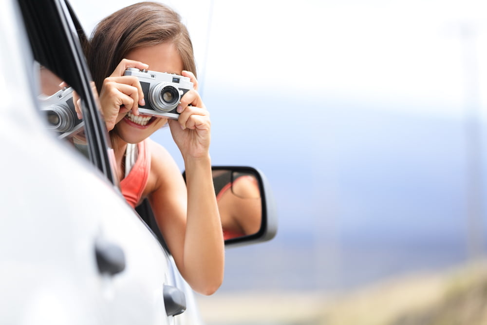 Girl passenger taking picture out of window