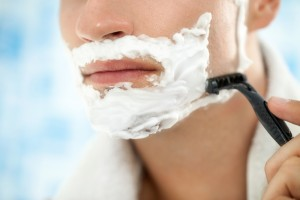 male shaving with razor