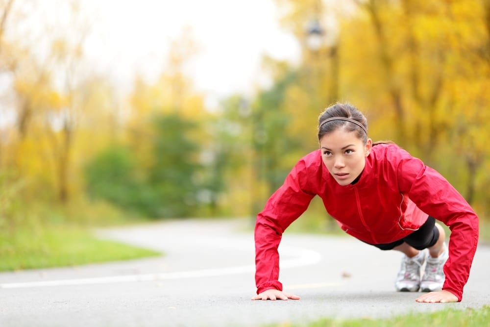 Fitness woman doing push-ups during outdoor cross training