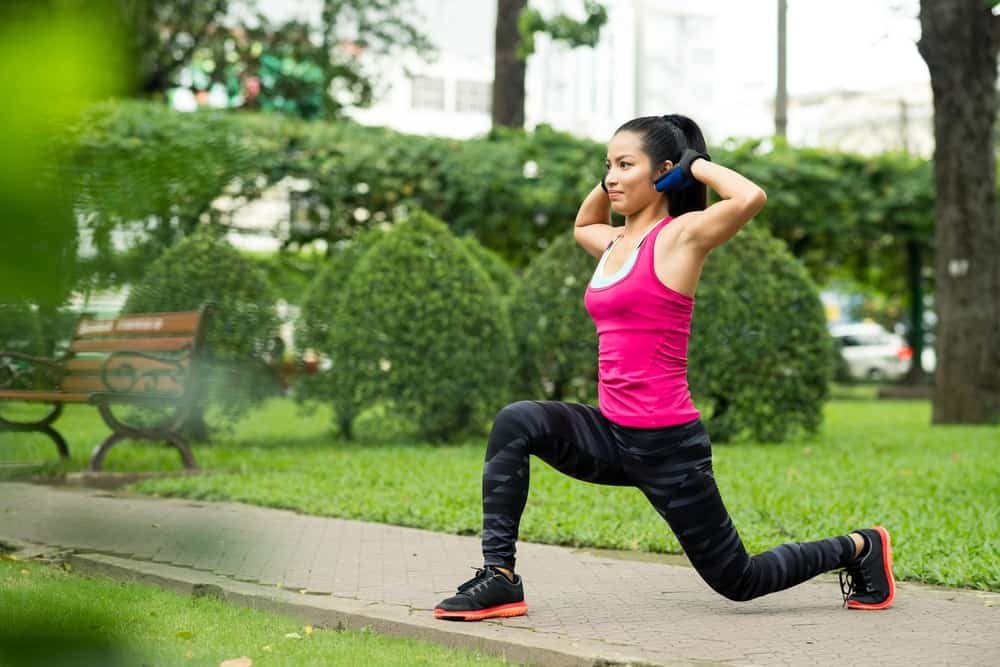 woman doing lunge exercise in park